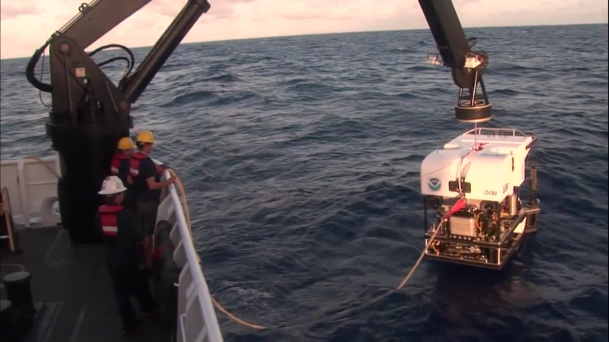 CIRCA 2010s - A deepwater submarine is lowered into the water, shots from the deepwater exploration of the Mariana Trench, 2016