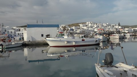Panoramic view of Paros island popular tourist attraction, Naousa town.  Promenade zone along port with restaurants and shops. Harbor of Aegean Sea, boats and yachts in quay at calm morning. Greece