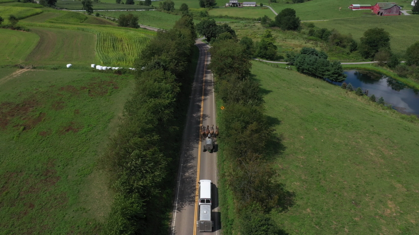 WILMINGTON, PENNSYLVANIA - 11 AUG 2019: Aerial Ohio Amish four horse farm team on highway road. Settled 1791. Old Amish Mennonite settlement. Rural old order. Farming landscape.