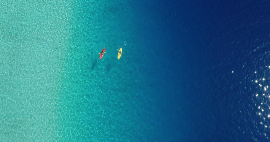 Wide aerial view of two kayakers paddling in a lagoon with pristine blue ocean water on a sunny sparkling day, amazing kayak adventures, adventurous couple kayaking together