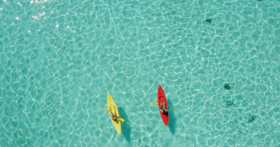 Aerial view of adventurous couple ocean kayaking together in pristine blue lagoon with sunny light textures refracting on the water surface, leisure kayaking tourism