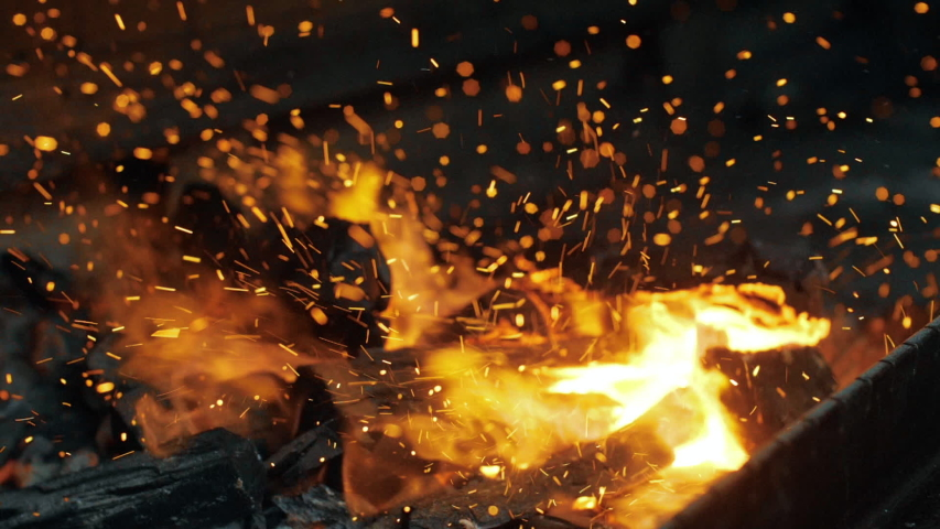 Closeup shot of fire sparks moving on dark at black background coming from brightly burning warm | Shutterstock HD Video #1036462502