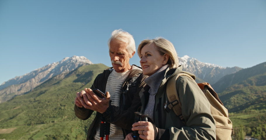 Senior caucasian couple having a nordic walk in mountains, then stopping to take a picture with smartphone. Old people traveling together after retirement - pension, tourism concept 4k | Shutterstock HD Video #1036468097