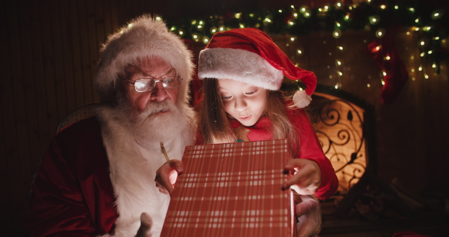 Santa claus sitting on his rocker with little caucasian girl sitted on his knee, opening up a gift with something special together - christmas spirit, holidays and celebrations concept 4k footage