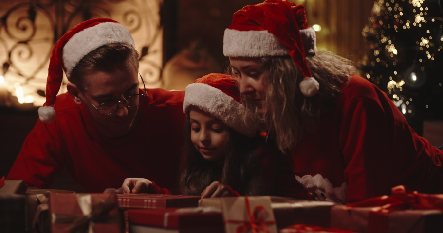 Caucasian family of three sitting in decorated room near christmas tree, little girl opening her christmas gift with something special - christmas spirit, togetherness concept 4k footage   Shutterstock HD Video #1036468142