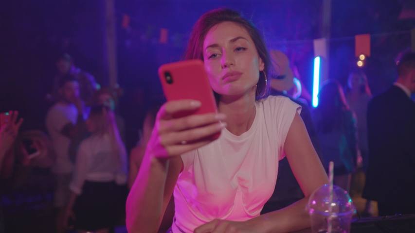 Portrait of bored attractive girl sitting alone on bar drinking cocktail at night. Gorgeous young woman with sad expression using smartphone gadget staying at party.