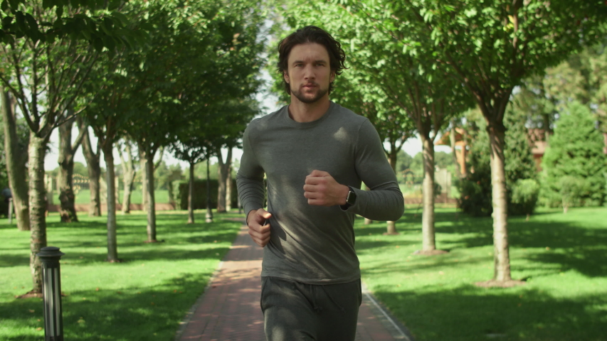 Attractive man, guy jogging in the park on a background of trees, fitness watch Royalty-Free Stock Footage #1036492628