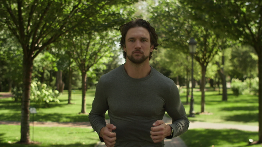 Movement to the target. Athletic man. The guy on a morning run in the park on a background of trees, Close-up, fitness watch. Royalty-Free Stock Footage #1036492667