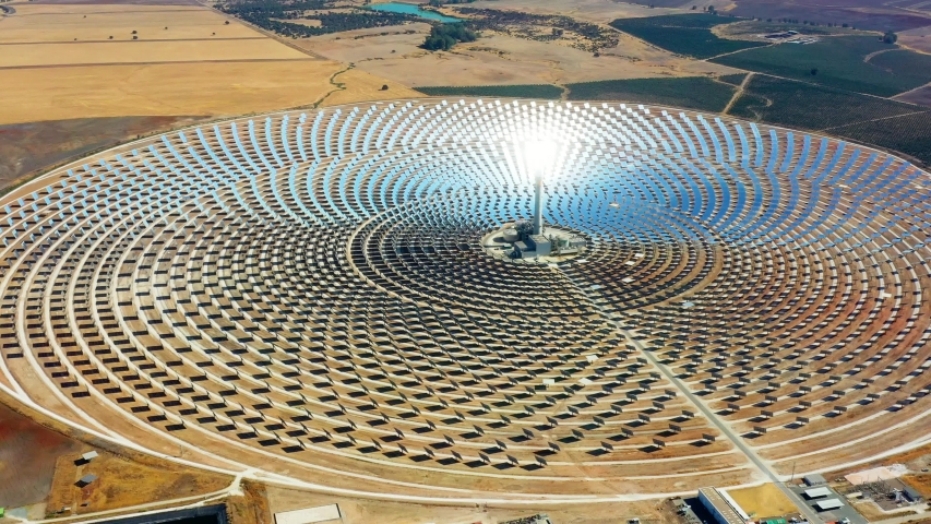 Aerial view of a large solar thermal plant uses mirrors that focus the sun's rays on a collection tower to produce renewable and pollution-free energy. | Shutterstock HD Video #1036501151