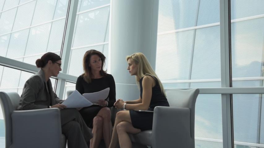 Caucasian businesswomen holding paperwork and talking
