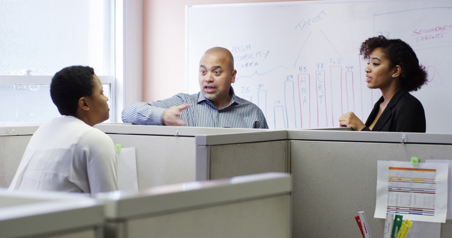 Business people talking in meeting at cubicles with whiteboard