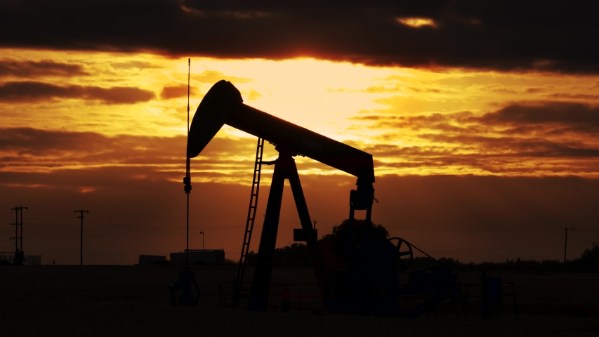 Pump jack. Oil well, close up.Silhouette of an oil pump jack on rig as the sun sets in the background. An oil pump jack on the middle of the wheat field with the beautiful sunset sky.
