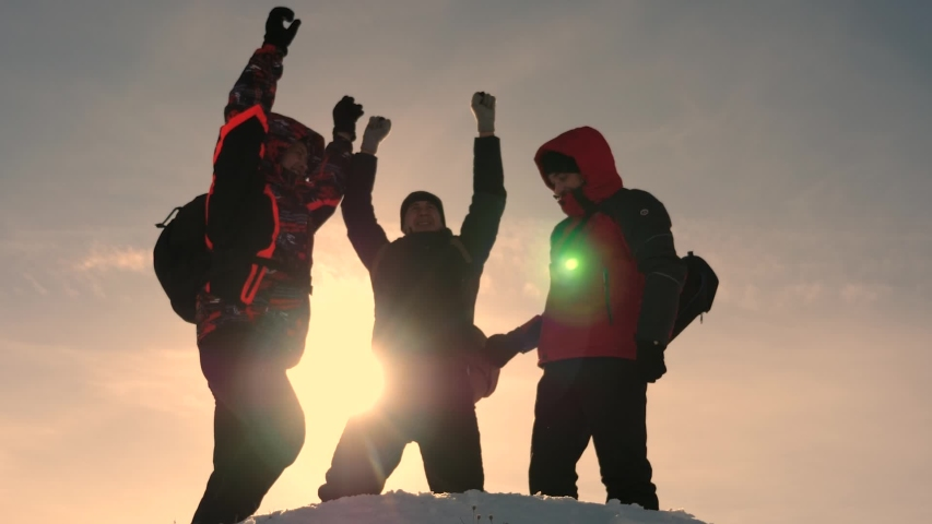 Alaskan travelers go to the top of a snowy hill and rejoice in victory against winter sunset. team work of people. business teamwork, victory and success. Tourists met on top of success.