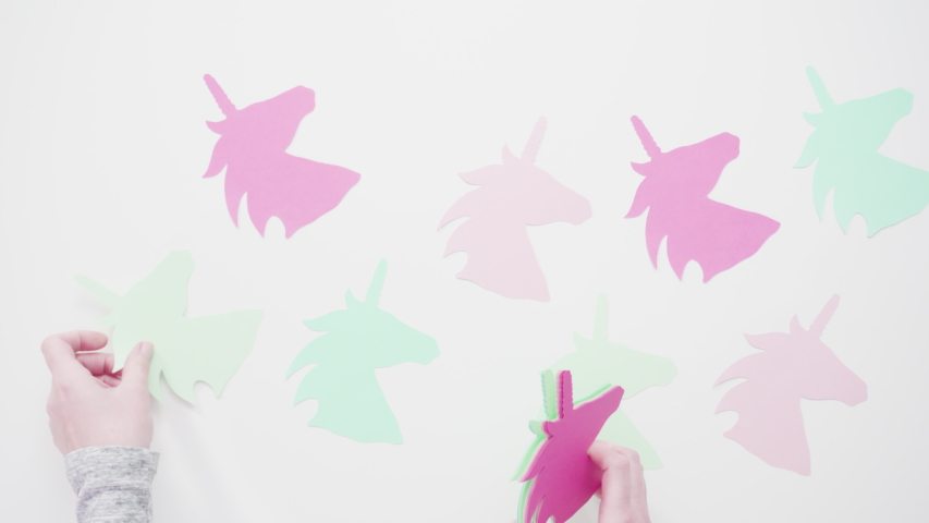 Colorful unicorn paper cutouts on a white background. | Shutterstock HD Video #1036571564