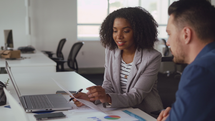 Young smiling african american businesswoman explaining new ideas and plans to male colleague holding chart in hand at desk in office | Shutterstock HD Video #1036574912