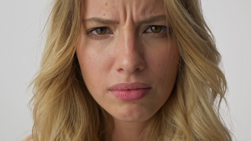 Cropped view of displeased young blonde woman becoming disgusted and grimacing while looking at the camera over gray background isolated