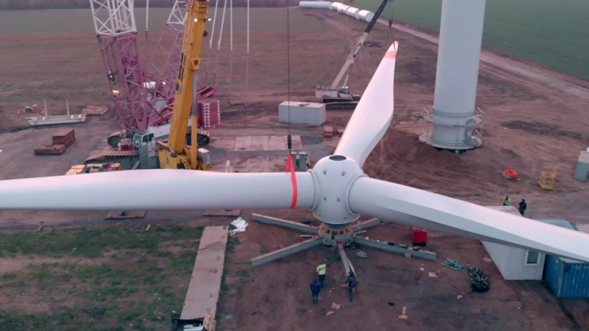 Building process of wind energy power tower mill, under construction. Assembling blades, turbine, rotor. Green, clean, renewable energy. Aerial footage.