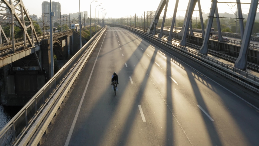 Aerial drone view of cyclist riding over the bridge, industrial landscape of big city | Shutterstock HD Video #1036586360