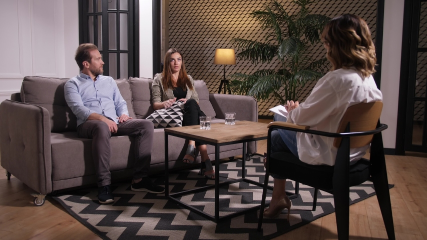 Adult couple sitting on sofa on appointment and discussing relationship problems with family counselor. Nervous wife drinking water while calm husband expressing his point of view on crisis situation #1036597367