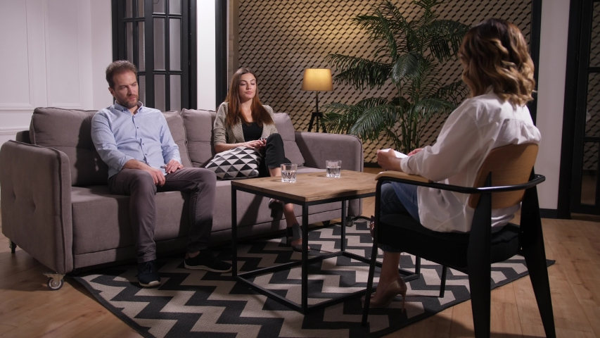 Nervous wife sitting on sofa in front of marriage counselor, drinking water to calm down and emotionally explaining difficult situation in family. Husband calmly listening to wife's accusations | Shutterstock HD Video #1036597370
