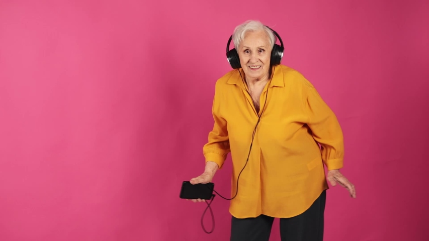 A very old grandma cool incendiary dancing to the music in big headphones from the phone. isolated, pink background. slow motion