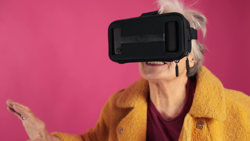 Very old grandma , dressed fashionably and youth takes off his glasses virtual reality . VR glasses. isolated, pink background.