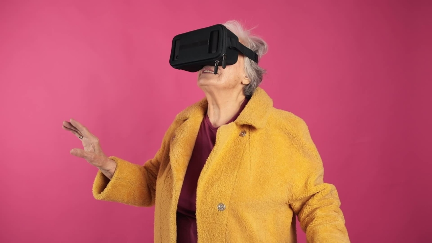 Very old grandma, dressed fashionably and youth use VR glasses. isolated, pink background.