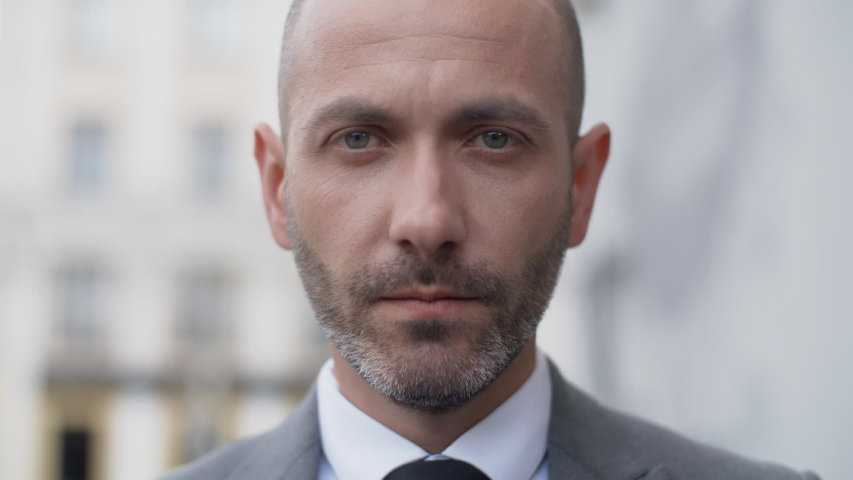 Close up attractive middle aged bearded man in business suit looking into camera seriously in the city outdoors. Portrait of handsome serious male businessman standing on office porch | Shutterstock HD Video #1036604147