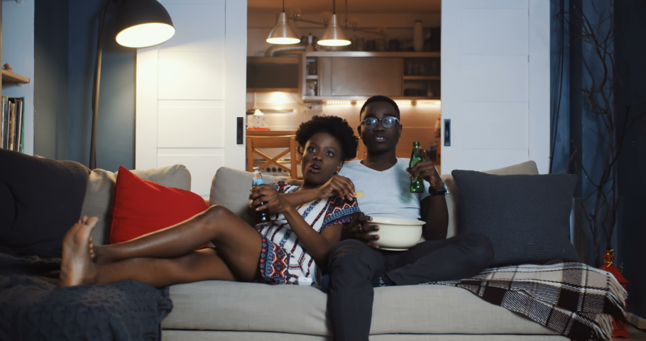 Happy young African millennial romantic couple watching movies at home on the couch, eating snacks talking slow motion. | Shutterstock HD Video #1036605377