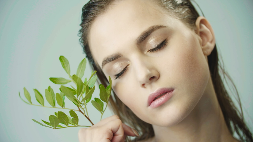 Face of young girl with clean smooth skin and small branch in hands. Natural and organic cosmetics, skin care, shampoo. Natural make-up. Girl holds leaves on her cheek. Opens eyes. Wet hair. Royalty-Free Stock Footage #1036612442