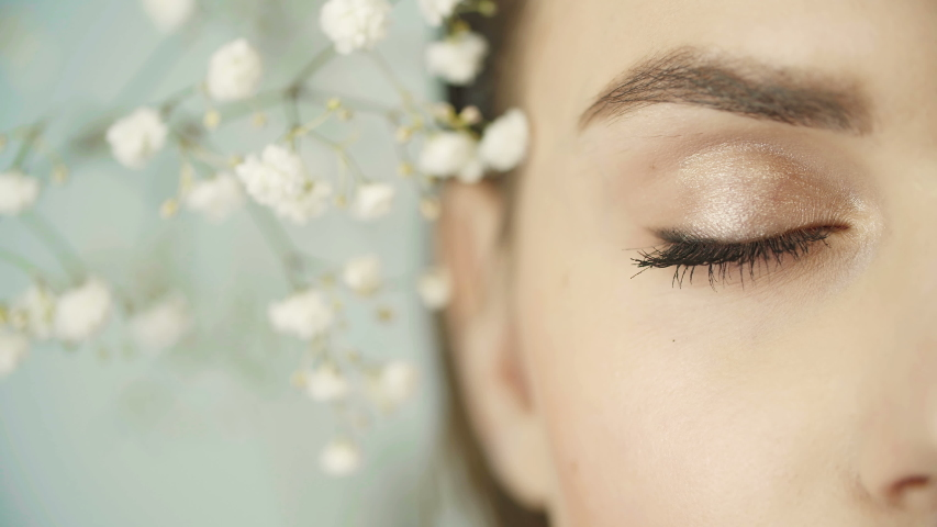 Close-up of girl's eyes with clean smooth skin, nude make-up. Girl's face among gypsophila plants. In studio. Girl opens her eye looking at camera. Vision. Beautiful eye. Half face in frame.