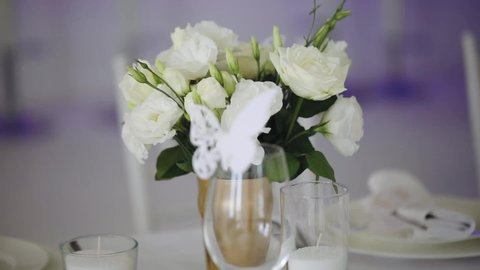 fashionable wedding table decoration with white flower bouquets and paper butterflies slow motion closeup