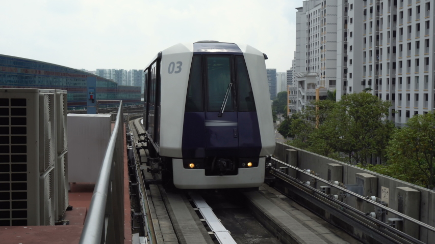 Futuristic Autonomous Train Driving on Elevated Tracks Arriving at Station in City of Singapore | Shutterstock HD Video #1036614962