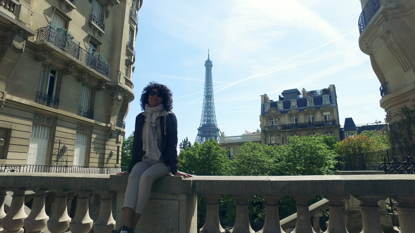 Happy aucasian female model traveling in France, Europe. Travel concept with panoramic view of Eiffel Tower and old traditional street alley pavement and buildings, cinematic steadicam shot
