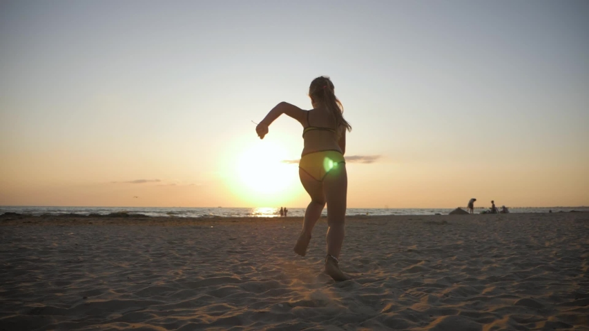 Adorable little girl running on tropical beach. Silhouette of happy child running in beautiful sunset light. Kid feet walking on wet sand in along a tropical beach. Slow motion, back view. #1036622228