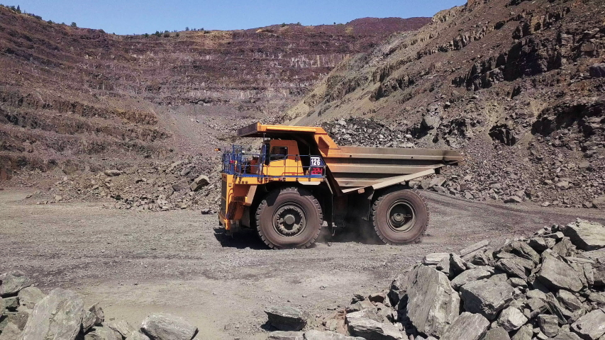Aerial view A mining truck is driving an iron ore mine loaded with ore.
