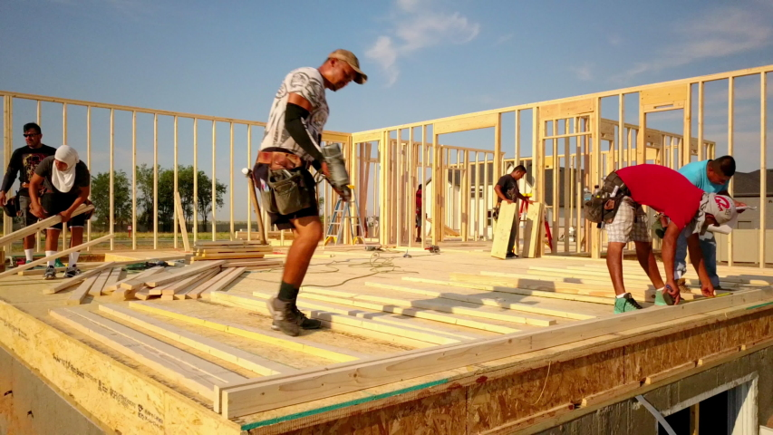 Layton , Utah / United States - 08 25 2019: A group of construction workers putting together the studs for walls and nailing them down. While they build the house.