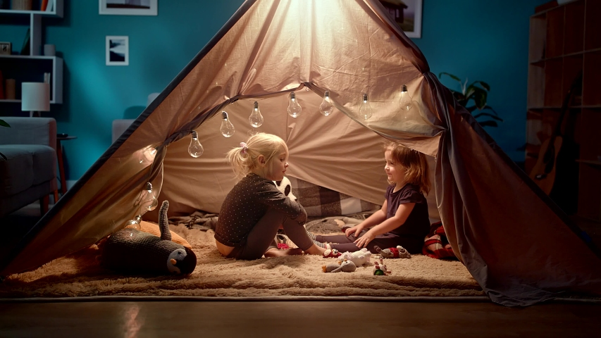 Two sisters play with toys in a toy tent in the room | Shutterstock HD Video #1036665071