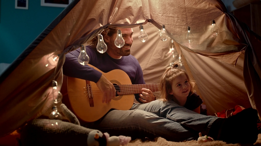 Dad plays the guitar for a little daughter in a kid's tent