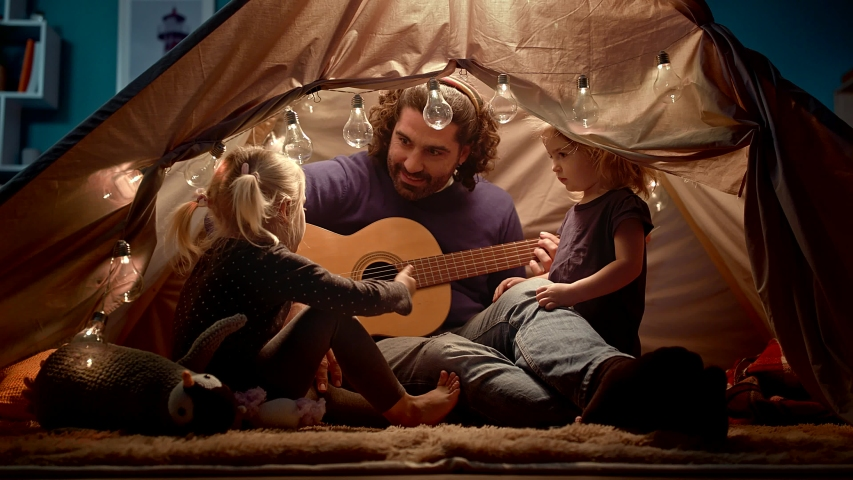 Dad plays the guitar and sings songs in a kid's tent