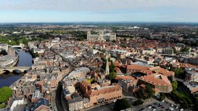 Aerial footage of the town of York located in North East England and founded by the ancient Romans, the footage shows the York Minster Historical Cathedral in the main town centre along the river.