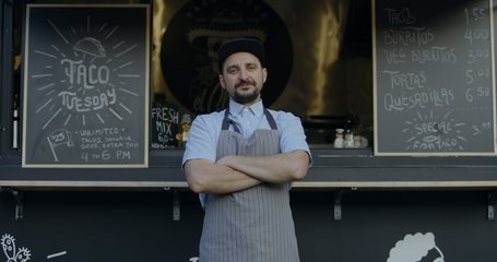 MED portrait Happy smiling middle-aged small business owner posing near his Mexican food truck. 4K UHD RAW graded footage