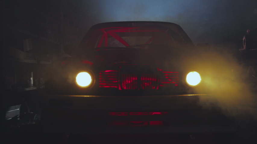 Close-up of Real Classic Luxury Vintage Car with Bright Headlights in Futuristic Garage with Neon Color. Vehicle Turned On Cool Blurred Headlights. Warm Smoke Comes in Building.
