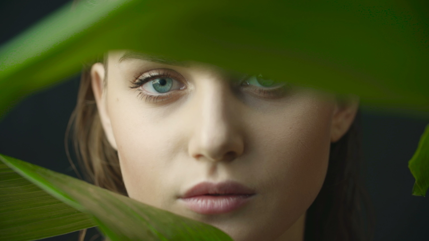 Face of girl with clean skin with natural makeup among exotic plants on a dark background in studio. Advertising of natural and organic cosmetics. Face of woman through large green leaves.