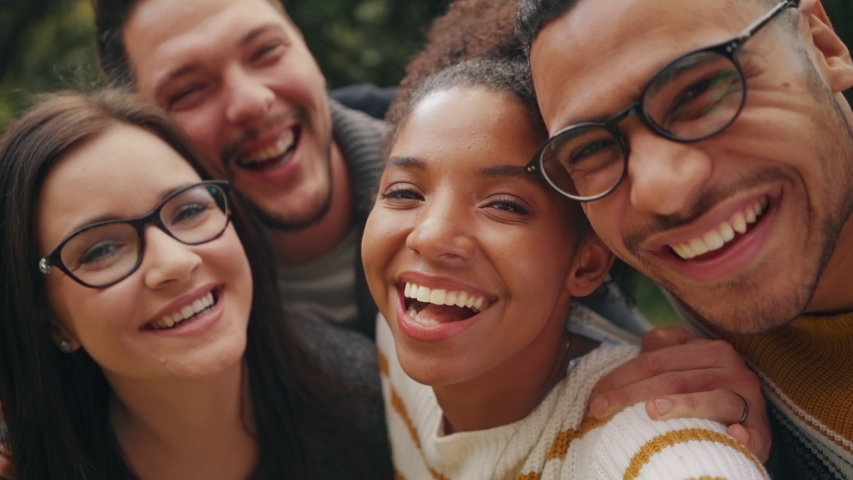 Smiling African Brazilian American young woman posing with her friends and making funny faces in front of camera whilst taking a selfie | Shutterstock HD Video #1036749647