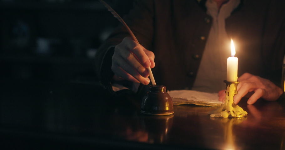 wide shot 1700s man writing with quill pen by candle light