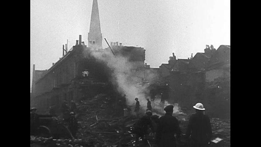 CIRCA 1940s - British civilians make their way through ruins in the aftermath of a Nazi air raid, during World War 2, in 1940.