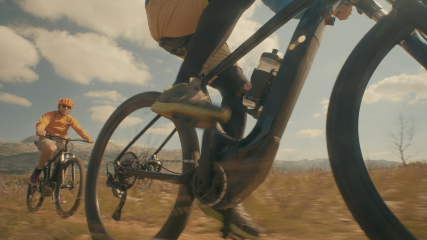 Low angle shot of two friends cycling through the desert   Shutterstock HD Video #1036762487