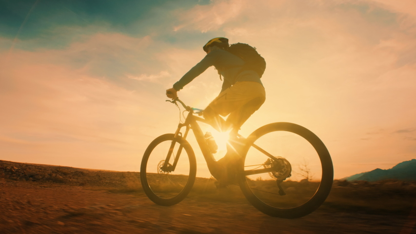 Low angle shot of a man cycling at sunset