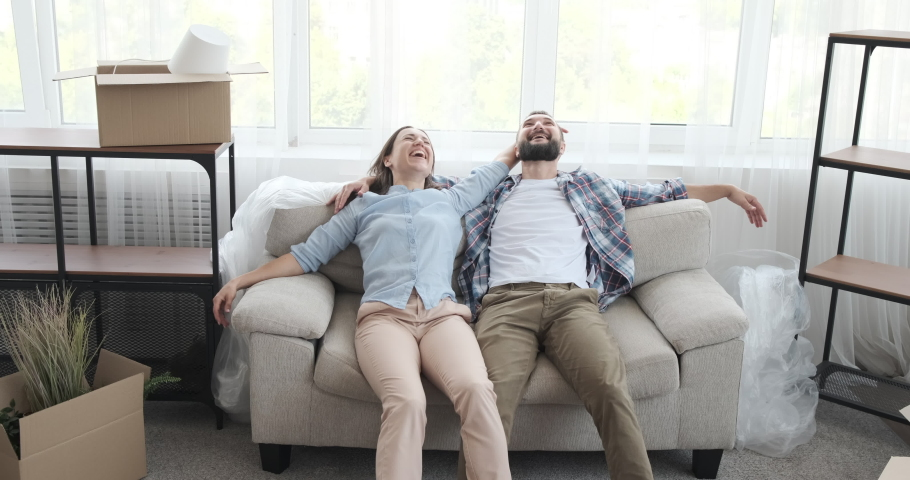 Happy couple falling on sofa in new house #1036763489